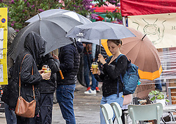 Licensed to London News Pictures. 16/05/2021. London, UK. Members of the public enjoy a takeaway drink while waiting for an outside table at a restaurant in Wimbledon Village, South West London make the most of the bad weather today as miserable May continues with grey skies and more rain with temperatures down to 14c. Weather forecasters predict yet more showers for the rest of the weekend and into next week as the bad weather continues. Photo credit: Alex Lentati/LNP