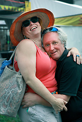 28 April 2013. New Orleans, Louisiana,  USA. .Faces in the crowd. A cuddle at the New Orleans Jazz and Heritage Festival. .Photo; Charlie Varley.