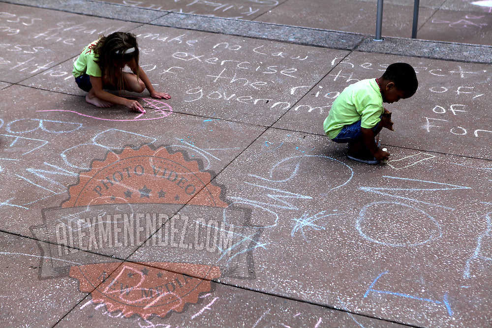 """Children use chalk to scribble messages as other activists take part in a rally on the steps of city hall in downtown Orlando, Florida on Saturday, May 5, 2013. The protesters gathered to support a global protest named  """"March Against Monsanto,"""" demanding a stop to the use of agrochemicals and the production of genetically modified food, which according to them has harmful health effects, causing cancer, infertility and other diseases. Marches and rallies against seed giant Monsanto were held across the U.S. and in dozens of other countries. (AP Photo/Alex Menendez)"""