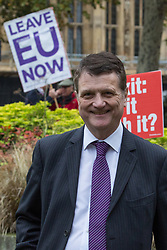 London, UK. 16th November, 2018. Gerard Batten, Leader of UKIP, appears on College Green in Westminster as uncertainty continues around the survival of Prime Minister Theresa May's Government and the number of letters of no confidence submitted to the 1922 Committee. Anti-and pro-Brexit activists stand behind him holding placards.