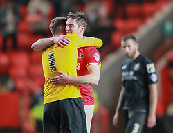 A dejected Bournemouth Steve Cook looks on as Charlton Athletic's Dorian Dervite celebrates scoring with a kiss from Ben Hamer - Photo mandatory by-line: Robin White/JMP - Tel: Mobile: 07966 386802 18/03/2014 - SPORT - FOOTBALL - The Valley - Charlton - Charlton Athletic v Bournemouth - Sky Bet Championship