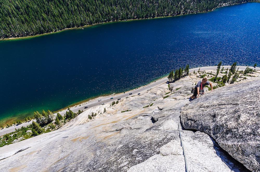 Rock climber on Stately Pleasure Dome above Tenaya lake, Tuolumne Meadows, Yosemite National Park, California USA