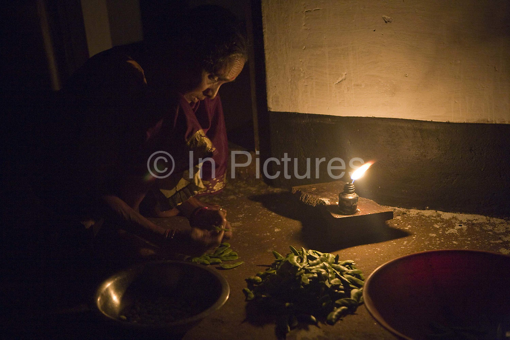 Elderley Indian woman cooking by candlelight on the floor of a hut. Coorg or Kadagu is the largest coffee growing region of India, in the state of Karnataka, the inhabitants - the Kodavas have been cultivating crops such as coffee, black pepper and cardamon for many generations.