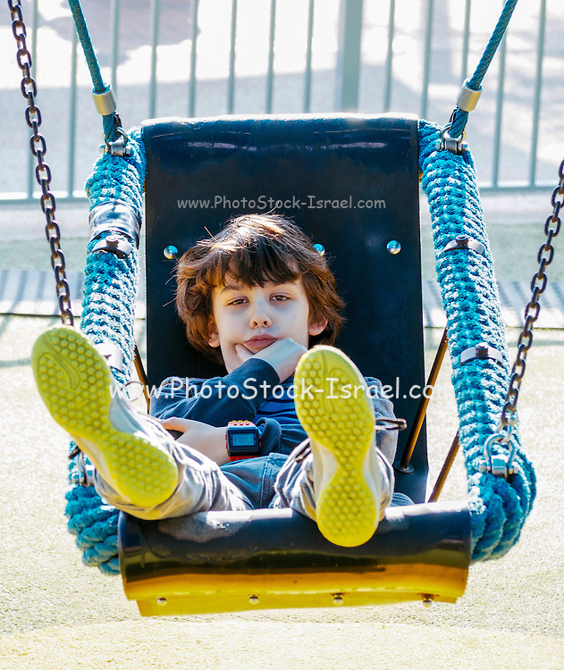 contemplating boy on a swing in a playground