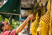 "12 NOVEMBER 2012 - BANGKOK, THAILAND:   A man paints a statue of the Buddha in front of his shop on Bamrung Muang Street in Bangkok. Thanon Bamrung Muang (Thanon is Thai for Road or Street) is Bangkok's ""Street of Many Buddhas."" Like many ancient cities, Bangkok was once a city of artisan's neighborhoods and Bamrung Muang Road, near Bangkok's present day city hall, was once the street where all the country's Buddha statues were made. Now they made in factories on the edge of Bangkok, but Bamrung Muang Road is still where the statues are sold. Once an elephant trail, it was one of the first streets paved in Bangkok. It is the largest center of Buddhist supplies in Thailand. Not just statues but also monk's robes, candles, alms bowls, and pre-configured alms baskets are for sale along both sides of the street.    PHOTO BY JACK KURTZ"