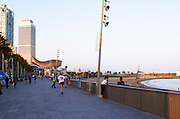 Beach side walking path to the Olympic Village with bronze sculpture Peix d'Or, the Gold Fish, by Frank Gehry and high rise buildings. Barcelona, Catalonia, Spain.