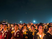 05 DECEMBER 2013 - BANGKOK, THAILAND: Thai civil servants hold candles during a candlelight service for the King. Thais observed the 86th birthday of Bhumibol Adulyadej, the King of Thailand, their revered King on Thursday. They held candlelight services throughout the country. The political protests that have gripped Bangkok were on hold for the day, although protestors did hold their own observances of the holiday. Thousands of people attended the government celebration of the day on Sanam Luang, the large public space next to the Grand Palace in Bangkok.     PHOTO BY JACK KURTZ