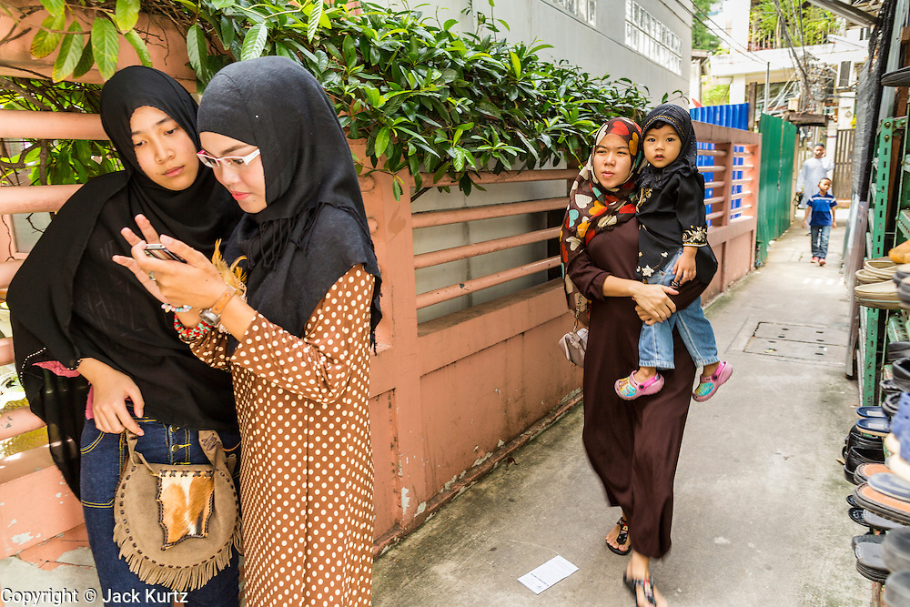 """08 AUGUST 2013 - BANGKOK, THAILAND: Thai Muslim girls look at their smart phone in alley next to Haroon Mosque in Bangkok after Eid al-Fitr services. Eid al-Fitr is the """"festival of breaking of the fast,"""" it's also called the Lesser Eid. It's an important religious holiday celebrated by Muslims worldwide that marks the end of Ramadan, the Islamic holy month of fasting. The religious Eid is a single day and Muslims are not permitted to fast that day. The holiday celebrates the conclusion of the 29 or 30 days of dawn-to-sunset fasting during the entire month of Ramadan. This is a day when Muslims around the world show a common goal of unity. The date for the start of any lunar Hijri month varies based on the observation of new moon by local religious authorities, so the exact day of celebration varies by locality.      PHOTO BY JACK KURTZ"""