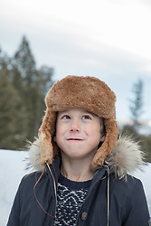 boy in a winter hat looking up to the sky