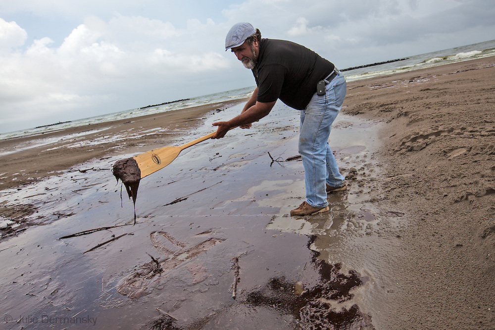 Chris Hernandez, Street Superintendent of Grand Isle puts an paddle into an oil patch on Grand Isle beack showing how thick the oil is while pointing out the lack of clean up crews on the beach.  Oil from the BP oil spillcontaminated the marshes and washed up on the shores of bird estuaries along the Gulf Coast.
