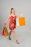Excited young blond woman in colourful summer dress out shopping On white Background