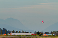 A hot air balloon over farmland in Surrey British Columbia.  Photographed from Blackie Spit at Crescent Beach in Surrey, British Columbia, Canada