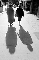 Black and white photo, women walking, Segovia, Spain.