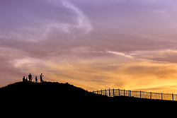 Holidaymakers in silhouette watch a spectacular sunset break over Porth Island in Newquay, Cornwall.