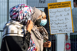 © Licensed to London News Pictures. 19/09/2020. London, UK. A group of women wearing face mask  walk past a sign outside a Covid-19 testing centre Edmonton, North London. The UK government is considering rationing Coronavirus tests for the general public has seen an increased demand for Covid-19 tests in recent days and a rise of over 3,500 daily. The British Prime Minister Boris Johnson has stated a second wave of Covid-19  was inevitable. Photo credit: Ray Tang/LNP