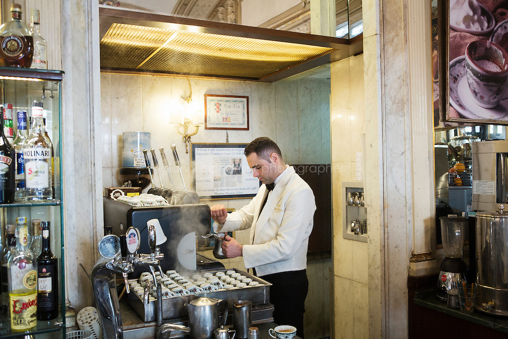 NAPLES, ITALY - 12 DECEMBER 2014: A barista prepares espresso coffees at the Storico Gran Caffè Gambrinus, a cafè in Naples, Italy, on December 12th 2014. The Storico Gran Caffè Gambrinus claims to have launched the tradition of the suspended coffee in the late 19th century.<br /> <br /> <br /> A caffè sospeso,or suspended coffee, is a cup of coffee paid for in advance as an anonymous act of charity. The tradition began in the working-class cafés of Naples, where someone would order a sospeso, paying the price of two coffees but receiving and consuming only one. A poor person enquiring later whether there was a sospeso available would then be served a coffee for free.