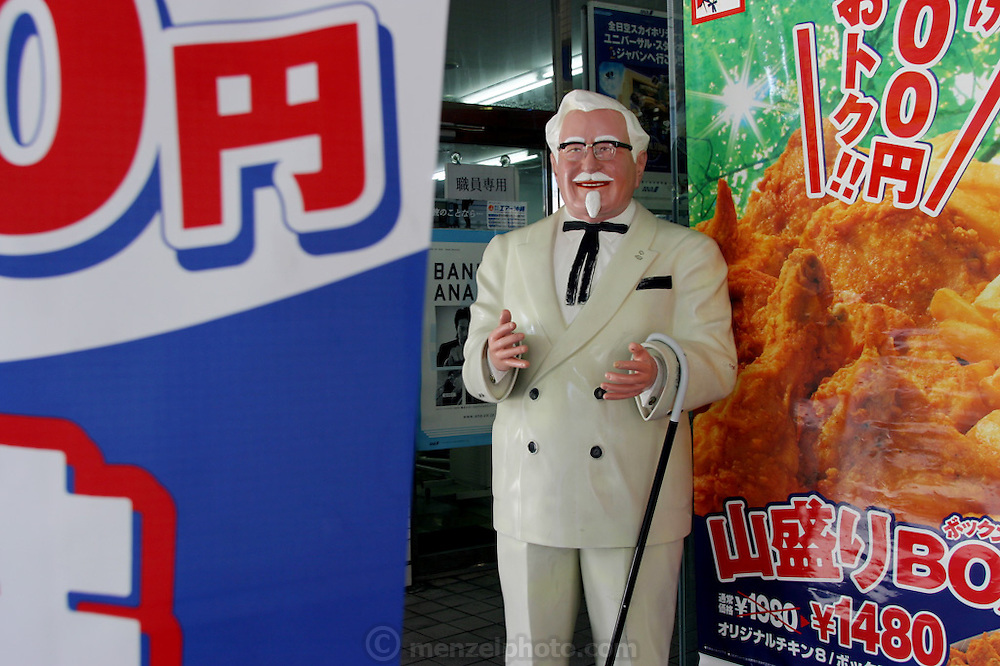 Iconic Colonel Sanders statue with signs in front of KFC chicken fast food restaurant in Naha City, Okinawa, Japan. (Supporting image from the project Hungry Planet: What the World Eats)