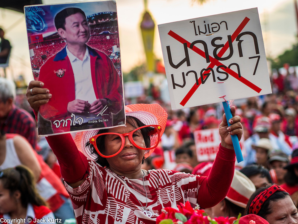 17 MAY 2014 - BANGKOK, THAILAND: A Red Shirt supporter with a photo of exiled former Prime Minister Thaksin Shinawatra at a Red Shirt rally on Aksa Road in Bangkok. Thousands of Thai Red Shirts, members of the United Front for Democracy Against Dictatorship (UDD), members of the ruling Pheu Thai party and supporters of the government of ousted Prime Minister Yingluck Shinawatra are rallying on Aksa Road in the Bangkok suburbs. The government was ousted by a court ruling earlier in the week that deposed Yingluck because the judges said she acted unconstitutionally in a personnel matter early in her administration. Thailand now has no functioning government. Red Shirt leaders said at the rally Saturday that any attempt to impose an unelected government on Thailand could spark a civil war. This is the third consecutive popularly elected UDD supported government ousted by the courts in less than 10 years.    PHOTO BY JACK KURTZ