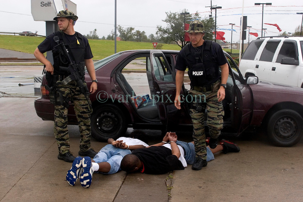 24th Sept, 2005. Hurricane Rita, Beaumont, Texas. Police from the Beaumont rapid reaction force arrest looters who they captured breaking into a Chevron petrol station just off interstate 10.