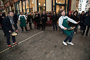 Shrove Tuesday festivities as competitors run the final of the Leadenhall Market Pancake Day Race on 13th February 2018 in London, United Kingdom. Competing teams of City workers outside The Lamb Tavern tackle the 25m course, competing to win the coveted frying pan trophy as they flip their way around the historic 14th century market.