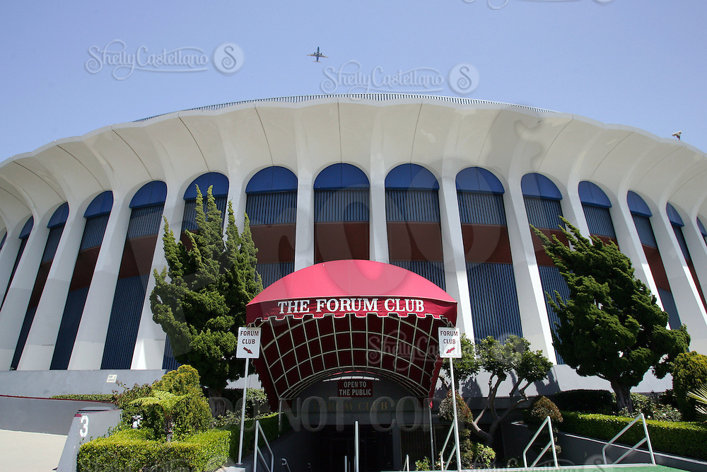 18 April 2006: An airplane makes its approach into LAX above the arena. Exterior view during the day of Sports Landmark Los Angeles Great Western Forum in Inglewood, California. 3900 West Manchester Boulevard, CA 90305. The Forum is currently owned by Forum Enterprises, Inc and managed by SMG. This arena was built in 1967 by Jack Kent Cooke, funded by Dr. Jerry Buss and Ogden Management, privately financed at a cost of $16 Million Dollars US.  It was the home to professional sports teams like the NHL Los Angeles Kings from 1967-1999, The NBA Los Angeles Lakers 1967-1999 and the WNBA Los Angeles Sparks as well as special events and concerts.  Located less than three miles from LAX airport and seats 17,505 fans inside the circular arena. Forum Club was home to many actors, celebrity and famous faces during the peak of this arena.  This is the main entrance to the club from the Prairie Avenue street.