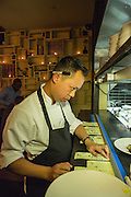 Chef Richard Kuo of Pearl & Ash overseeing orders as they come to the pass-through from the kitchen.