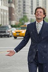 man in a three piece suit enjoying the rain in New York City
