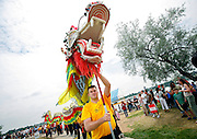 SHOT 7/28/2007 - Shaolin Hung Mei Kung Fu school student Tim Noonan (center, holding dragon's head) of Broomfield, Co. leads the procession during the Opening Ceremonies at the 2007 Colorado Dragon Boat Festival. Noonan and eight other students manned the dragon which was used as part of the Opening Ceremonies. The sport of Dragon boat racing is over 2000 years old and features teams of 18 paddlers - nine men and nine women plus someone to steer the boat all rowing to the beat of a drum and racing to a flag 200 meters away on Sloan's Lake in Denver, Co. Founded in 2001 to celebrate Denver?s rich Asian Pacific American culture, the Colorado Dragon Boat Festival has become the region?s fastest growing and most acclaimed new festival. Festival-goers get to explore the Asian culture through demonstrations, crafts, shopping, eating, and the growing sport of dragon boat racing. .(Photo by Marc Piscotty / © 2007)
