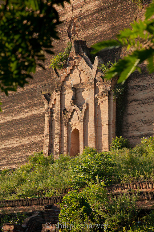 The vast Mingun Pahtodawgyi stupa was never completed, and now stands overgrown and cracked. Mingun, near Mandalay, Myanmar