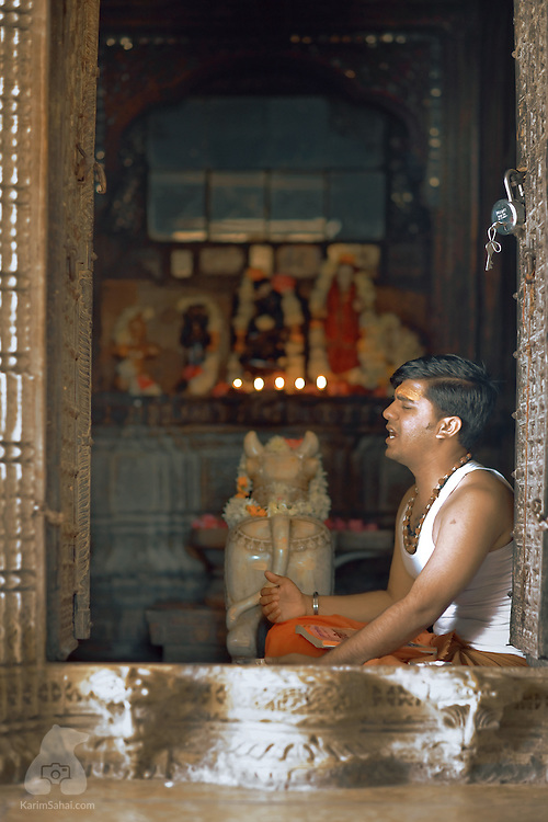 A young bhramin priest recites verses from the Vedas (sacred scriptures) at the Gajrupeshwar Mahadev temple. Mantras (sacred sounds) and vedic sacred texts rely on a centuries-old oral tradition of knowledge transmission from master to disciple. The language of the Vedas is Sanskrit.
