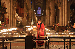 Cologne, Germany, Jan. 2012 -  The faithful light candles at the Cologne Dom Cathedral. Officially, Hohe Domkirche St. Peter und Maria (or The High Cathedral of Saints Peter and Mary), is a Roman Catholic church in Cologne, Germany. It is the seat of the Archbishop of Cologne and the administration of the Archdiocese of Cologne. It is renowned monument of German Catholicism and Gothic architecture and is a World Heritage Site. It is Germany's most visited landmark, attracting an average of 20,000 people a day. The Cologne Cathedral was built between 1248 and 1880. It is 144.5 meters (474 ft) long, 86.5 m (284 ft) wide and its towers are approximately 157 m (515 ft) tall. The cathedral is the largest Gothic church in Northern Europe and has the second-tallest spire and largest facade of any church in the world. The choir has the largest height to width ratio of any medieval church. (Photo © Jock Fistick)