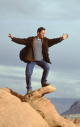 man balancing on a rock formation against the sky