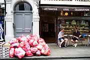 Commercial waste collection rubbish and recycling bags piled high along Old Compton Street in Soho, London, England, United Kingdom.