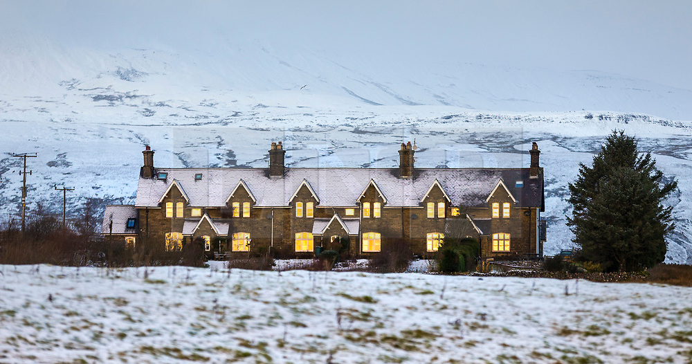 © Licensed to London News Pictures. 04/01/2021.Gearstones UK. The windows of a row of houses glow yellow as the rising sun reflects on them at the foot of Ingleborough Mountain this morning in the Yorkshire Dales. Photo credit: Andrew McCaren/LNP