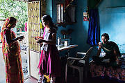 Video Volunteer videojournalist Niru J. Rathod (right), 24, looks through her video footage on her camera while her sister Mukta (center), 22,  attends to a tailoring customer at home in Surendranagar, Gujarat, India on 14 December 2012. While Niru's sisters have become seamstresses or housewives, Niru, the 8th child in a family of 11 girls born to a Dalit construction worker, has been using videography for social change since 2006. She shoots and produces her own short documentaries and is a committed video activist, having conducted hundreds of village video screenings where she also speaks to thousands of men, shattering their ideas about what a woman and a Dalit can do while bringing massive changes to the communities she documents. Photo by Suzanne Lee / Marie Claire France