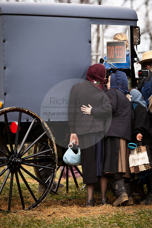 Amish girls look at a horse buggy during the Annual Mud Sale to support the Fire Department  in Gordonville, PA.
