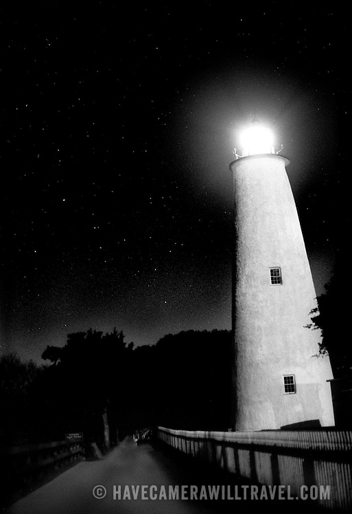 The lighthouse at Ocracoke Island, one of the southernmost islands on North Carolina's Outer Banks, at night, in black and white.