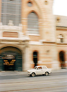 Small old car driving past the Great Market Hall, in Budapest, Hungary