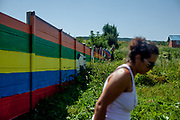 "The wall at the Roma settlement Ostrovany seen from the settlement. Veronika a Roma woman herself at the wall,""I live in the settlement. I work as assistant at the town hall. The fence is not dividing us in anything, we did not go to the gardens  anyway - sometimes some children were jumping over to get some fruits. There were other fences before. Children, not adults. I feel it is like a fence and not a wall. It is a normal solution. I understand the owners who had a problem with this. I would save also my property…that is normal."""