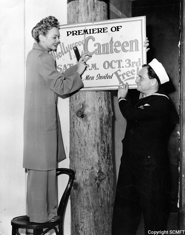 """10/42 Actress Leslie Brooks & Yoeman Seymour Rice hang a """"grand opening"""" sign announcing the opening of the Hollywood Canteen"""