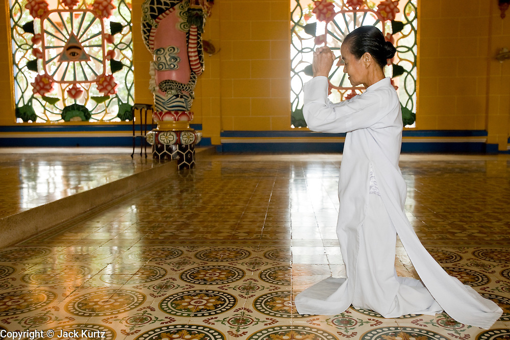 """10 MARCH 2006 - TAY NINH, VIETNAM: Women praying in the main Cao Dai Temple in Tay Ninh. The Cao Dai complex in Tay Ninh is the sect's headquarters. The Cao Dai religion is a blending of Buddhism, Confucianism, Taoism, Christianity and Islam. There """"saints""""  include Chinese leader Sun Yat Sen and French author Victor Hugo. There are about two million members of the Cao Dai religion in Vietnam. British author Graham Greene, who wrote about the Cao Dai in the """"The Quiet American"""" said the relegion was """"a Walt Disney fantasia of the East."""" Photo by Jack Kurtz / ZUMA Press"""