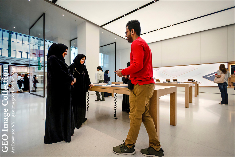 A salesman in the Apple Store in Mall of the Emirates talks with Arab shoppers.