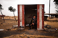 A rebel waits at a checkpoint on the road between Braga and Sirt between battles on March 5. 2011.