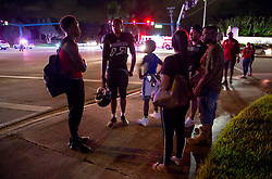 August 18, 2018 - Wellington, Florida, U.S. - A Palm Beach Central football player stands at the corner of Forest Hill Boulevard and Lyons Road after a shooting sent players and fans scattering in all directions. Two adults were shot Friday night at a football game between Palm Beach Central and William T. Dwyer high schools, authorities said. The gunfire sent players and fans screaming and stampeding in panic during the fourth quarter of the game at Palm Beach Central High School in Wellington, Florida on August 17, 2018. (Credit Image: © Allen Eyestone/The Palm Beach Post via ZUMA Wire)