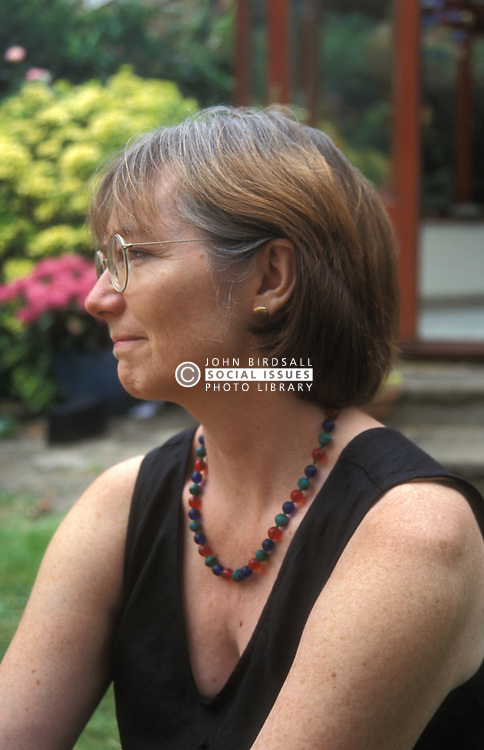 Portrait of 52 year old woman wearing glasses and black dress sitting in her garden UK