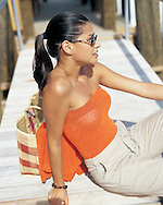 A beautiful young lady is sitting on a boat dock with her bag, waiting to travel by boat to some exotic destination.