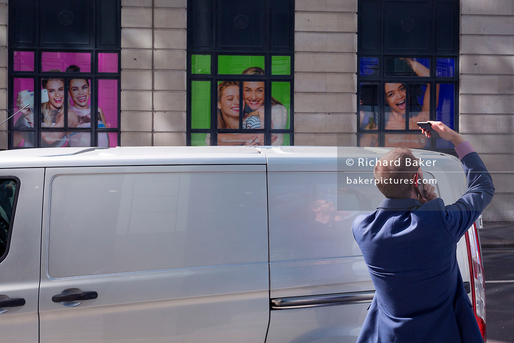 A man takes a picture with one mobile phone while talking into another in front of smiling Superdrug models, in the City of London, the capital's financial heart, on 25th September 2018, in London, England.