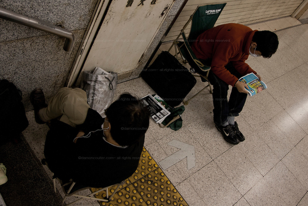 Homeless men read before they settling down for the night at Shibuya Station in Tokyo, Japan. Friday, October 10th 2009