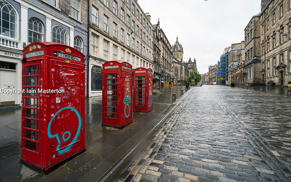 Edinburgh, Scotland, UK. 29 June, 2020. Many shops which have door access to the street are allowed to open for business in Scotland today. Despite cool temperatures, high winds and often heavy rain, some shops had queues outside in the morning. Tourist shops on the Royal Mile ( pictured) remained closed however, due to a lack of tourists,  and streets in the Old Town remained empty.  Iain Masterton/Alamy Live News
