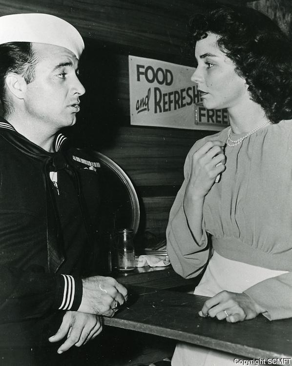 1944 Actress Jennifer Jones chats with a sailor at the Hollywood Canteen
